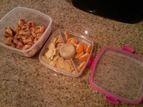 Salad To Go container packed with cheese tortellini in the lower portion, tangerine and pita chips in the upper portion, and hummus in the small round conatiner