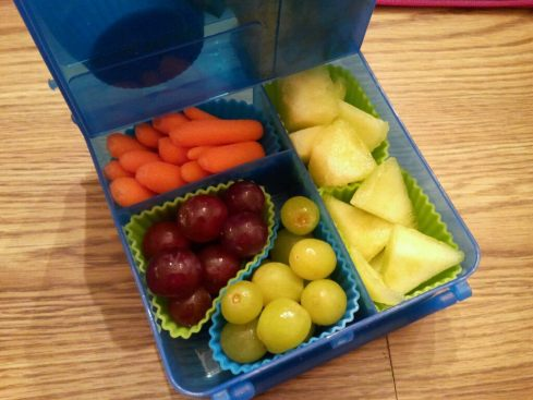 Bottom part of Bright Bin packed with baby carrots, grapes, and honeydew